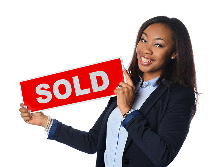 Woman in suit holding up a sign that says SOLD